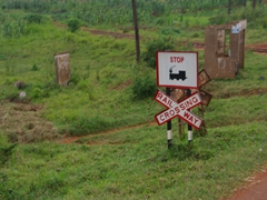 "Signpost for a ""Railway Crossing"" stop sign; near Kampala"