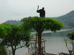 A gardener hacks away unwanted branches of a tree with a machete; Bunyonyi Overland Resort