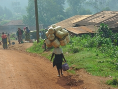 A woman balances a load of grass baskets on her head as she walks into Kabale