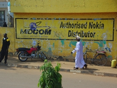 Robed men walk beside a Midcom wall advertisement; Kampala