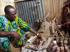 A fetisher explains the cures provided by several talismans blessed by his black magic; Akodessewa Fetish Market