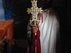 "A priest holds up a large cross inside the aptly named ""House of the Cross""; Lalibela"