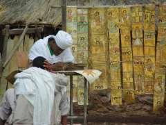 A priest works on painting religious scrolls; Lalibela