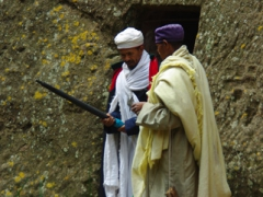 Two church leaders debate the merits of whether to bring along an umbrella or not; Lalibela
