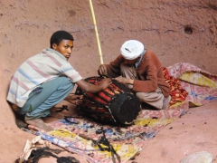 Two workers stitch up a drum just outside of Bete Merkorios (which partially collapsed due to an earthquake in the 16th Century); Lalibela