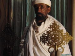 A priest holds up two crosses inside Bete Abba Libanos (House of Father Libanos); Lalibela
