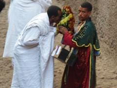 A worshipper fervently kisses the bible just outside Bete Medhane Alem; Lalibela