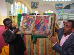 Church caretakers showing us an ancient bible (made of sheep or goat skin); Saint Mary of Zion Church in Axum