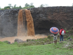 Marie stands next to a tout at the Blue Nile Falls