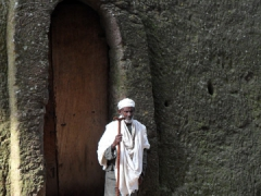 A religious caretaker stands guard outside the House of the Saviour of the World; Lalibela
