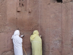 Two religiously devout women praying outside of the House of Mary; Lalibela