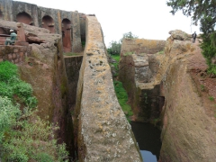 "View of ""Bete Gabriel and Rufael"", a twin rock hewn church which symbolizes both Heaven and Hell. The precarious rock ramp leading up to the church symbolizes heaven, while the underground water reservoir symbolizes hell. Locally, this is known as ""Meferareja""; Lalibela"