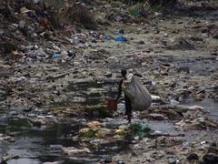Not an enviable job! A man sifts through a garbage strewn river in Dar Es Salaam