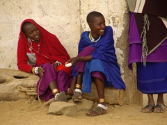 Maasai women joking around as they watch the men dance