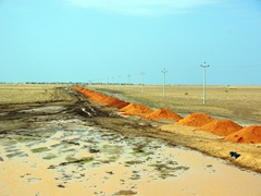 Orange dirt mounds as far as the eye can see while road works continue on a main road leading towards Khartoum
