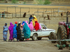 Brightly attired women hitch a ride on the back of a pickup truck