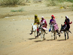 Four colorfully garbed Sudanese women riding donkeys caught our attention