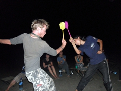 Lars and Lisa dance to techno music with fly swatters during our FDNCTP (First Day New Country Truck Party); Sudan bush camp