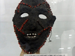 A face mask made from gourd covered in black wax and decorated with pennisetum grains (dura); Ethnographic Museum