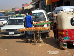 A bread seller attempts to gingerly make his way through the backlogged traffic of Omdurman Souq