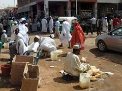 Sponge sellers hawk their wares to passersby; Omdurman Souq in Khartoum