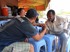 Ichiyo serves as referee in the arm wrestling competition between Lucky and a friendly Khartoum resident