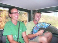 Sara laughs as Robby sighs in relief after getting a light breeze from a hand fan; Lope National Park jeep safari
