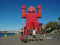 Bree, Becky, Lucky, Dowelly, Luke and Robby strike a pose in front of a massive coca-cola recycling project; Cape Town waterfront