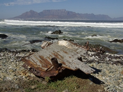 A washed up section of shipwreck on Robben Island with Table Mountain in the distance