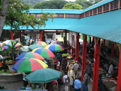 The umbrellas and overhang provide limited shade at Sir Selwyn's market; Victoria
