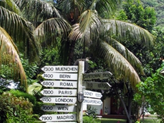 Signpost indicating various distances to world cities; entrance to Calou guesthouse; La Digue