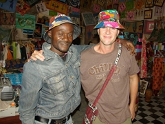 """Robby dons a """"happy hat"""" next to a friendly St-Louis shopkeeper"""