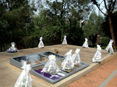 Several flower arrangements on one of the mass graves at the Genocide Museum, Kigali