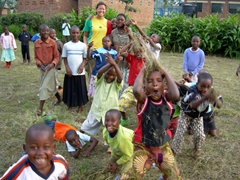 Becky taking a photo with rambunctious kids in Musanze