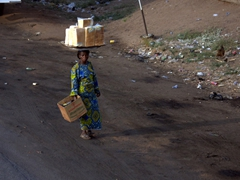 A bread seller balances her load while attempting to sell by the road side