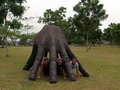 Lucky, Robby and Dowelly pose by a massive hand monument just outside the Calabar Museum