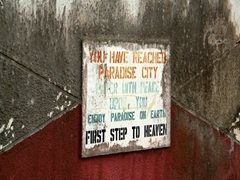"The ironic signpost of the very scary Paradise City Hotel aka ""First Step to Heaven"" (isn't that death?); Calabar"