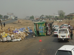 An overturned truck spills its precious cargo all over the highway; near Abeokuta