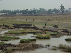 Bricks are handmade from the mud from this shallow pond; near Bida