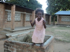 A jubilant girl poses for a photo outside Kande School