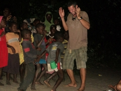 Robby laughs as he dances with Malawian kids; Kande Beach