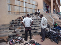 Lilongwe shoe vendor (the customer is at a lost to figure out which one he likes best!)