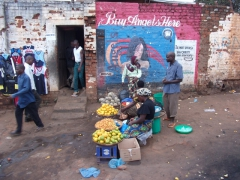 Fruit sellers in front of an Angels hair extension wall advertisement; Lilongwe