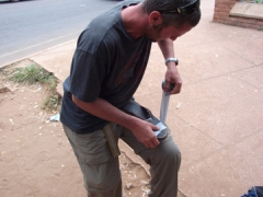 Robby taping his broken flip-flop to the amusement of locals; Lilongwe