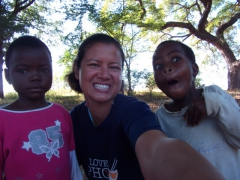 Becky takes a self portrait with two school children (one who clams up and the other who hams it up); Mphatso Children's Foundation