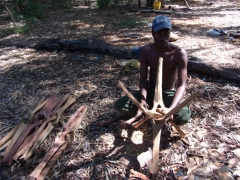 A carpenter demonstrating that all table legs are made from one piece of wood; Kande Beach