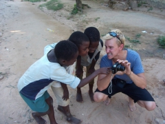 Scott grimaces as he shows the kids their own image; Kande Beach