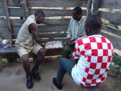 Locals playing checkers at a bush bar; Kande Beach
