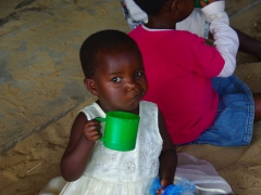 A young girl smirks as she has her photo taken during mid-morning break; Mphatso Children's Foundation
