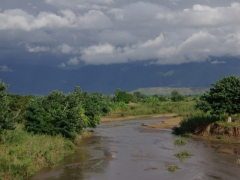 A river runs through it; storm clouds loom over a Lake Malawi tributary